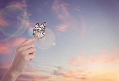 Woman holding beautiful rice paper butterfly against sunset sky, closeup
