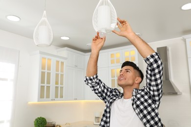 Man changing light bulb in lamp at home. Space for text