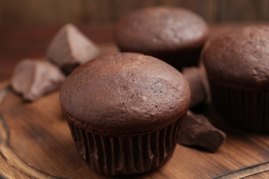 Delicious chocolate cupcakes on wooden board, closeup