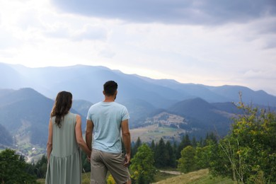 Couple enjoying beautiful mountain landscape, back view. Space for text