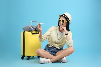 Happy female tourist with toy plane, suitcase and travel pillow on light blue background