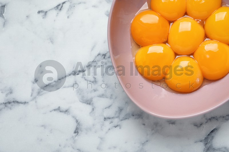 Bowl with raw egg yolks on white marble table, top view. Space for text