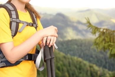 Woman with backpack and trekking poles hiking in mountains, closeup. Space for text