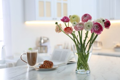 Beautiful fresh ranunculus flowers near cup of coffee, croissant and book on table in kitchen