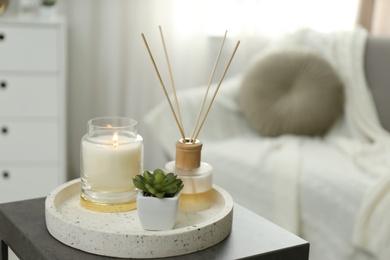 Air reed freshener, candle and plant on table in room, space for text