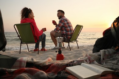 Couple resting near sea at sunset, view from camping tent