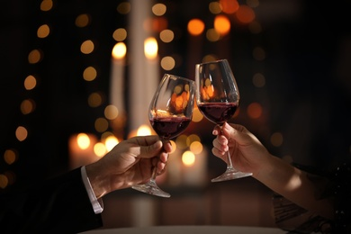 Couple clinking glasses at Valentine's day dinner in restaurant, closeup