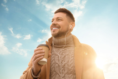 Man with cup of coffee on city street in morning
