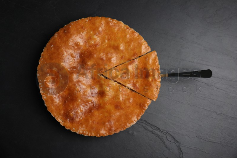 Delicious pie with meat on black table, top view