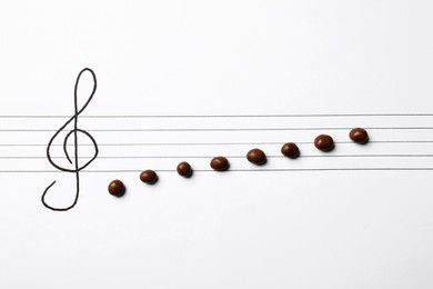 Music staff with treble clef and chocolate candies as notes on white paper, flat lay. Creativity concept