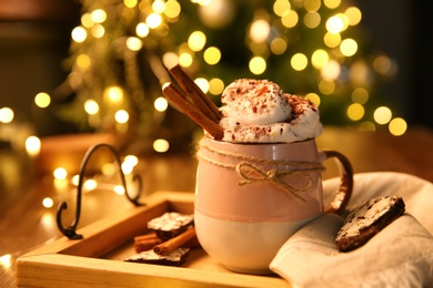 Tasty hot drink with whipped cream on table against blurred Christmas lights, closeup