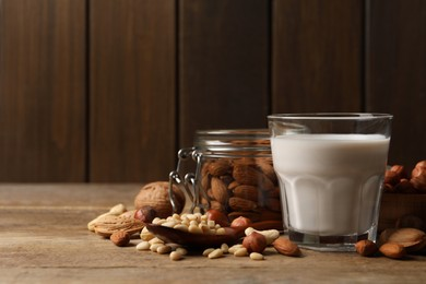 Vegan milk and different nuts on wooden table. Space for text