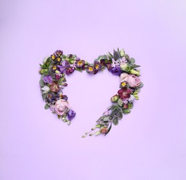 Beautiful heart made of different flowers on violet background, flat lay. Space for text