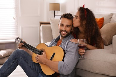 Lovely couple with guitar spending time together at home