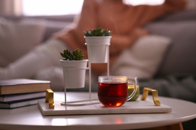 Woman relaxing at home, focus on tray with cup of tea and succulent plants. Cozy atmosphere
