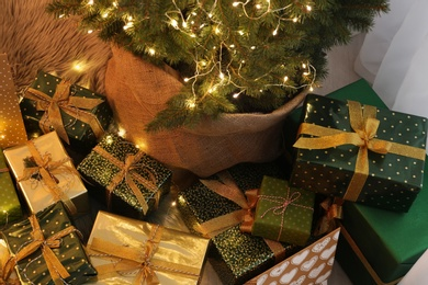 Many different gifts under Christmas tree indoors, above view