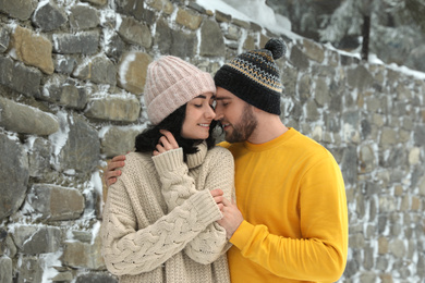 Lovely couple wearing warm sweaters and hats outdoors on snowy day. Winter season
