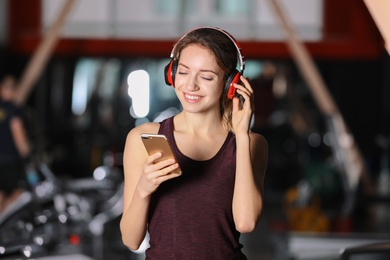 Young woman with headphones listening to music on mobile device at gym