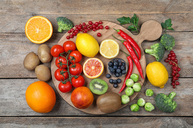 Different products rich in vitamin C on wooden table, flat lay