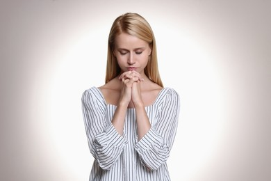 Religious young woman with clasped hands praying against light background