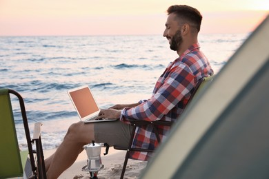 Man using laptop in camping chair on sandy beach