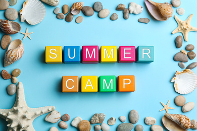 Colorful wooden cubes with phrase SUMMER CAMP on light blue background, flat lay