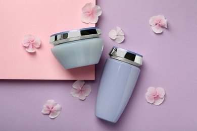 Hair care cosmetic products and petals on color background, flat lay