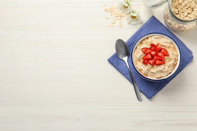 Tasty oatmeal porridge with strawberries served on white wooden table, flat lay. Space for text