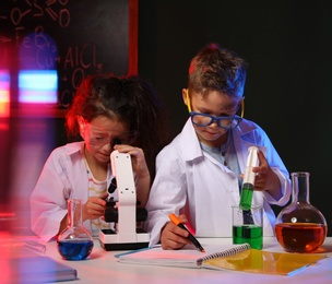 Children doing chemical research in laboratory. Dangerous experiment