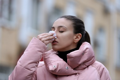 Ill woman with paper tissue sneezing outdoors