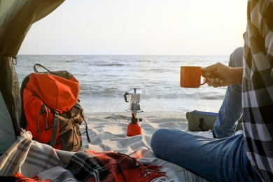 Man with cup of hot drink in camping tent, closeup