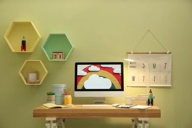 Stylish workplace with computer on wooden desk near light green wall. Interior design