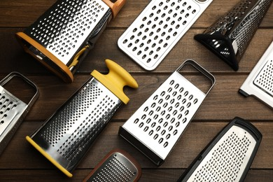 Different modern graters on wooden table, flat lay