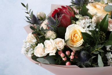Beautiful bouquet with roses on light blue background, closeup
