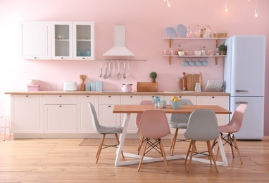Stylish pink kitchen interior with dining table and chairs