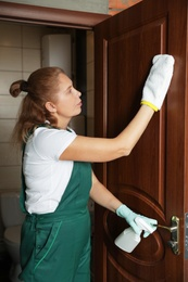 Professional janitor cleaning restroom door at home