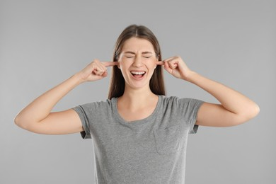 Emotional young woman covering her ears with fingers on grey background