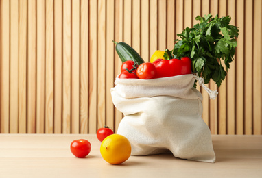 Cotton eco bag with vegetables and fruits on wooden table. Space for text