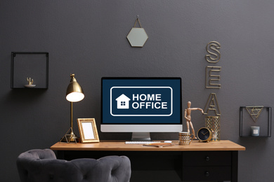 Modern computer with text HOME OFFICE on table indoors