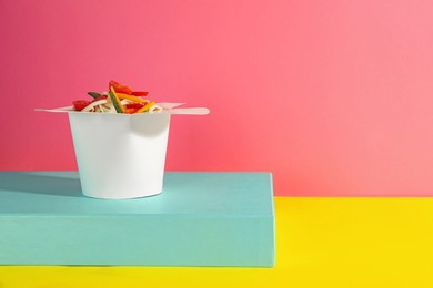 Box of vegetarian wok noodles on color background. Space for text