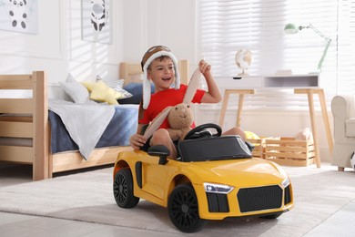 Cute little boy playing with stuffed bunny and big toy car at home