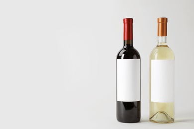 Bottles of delicious wines with blank labels on white background