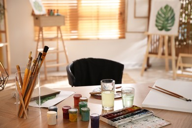 Paints and brushes on wooden table in art studio