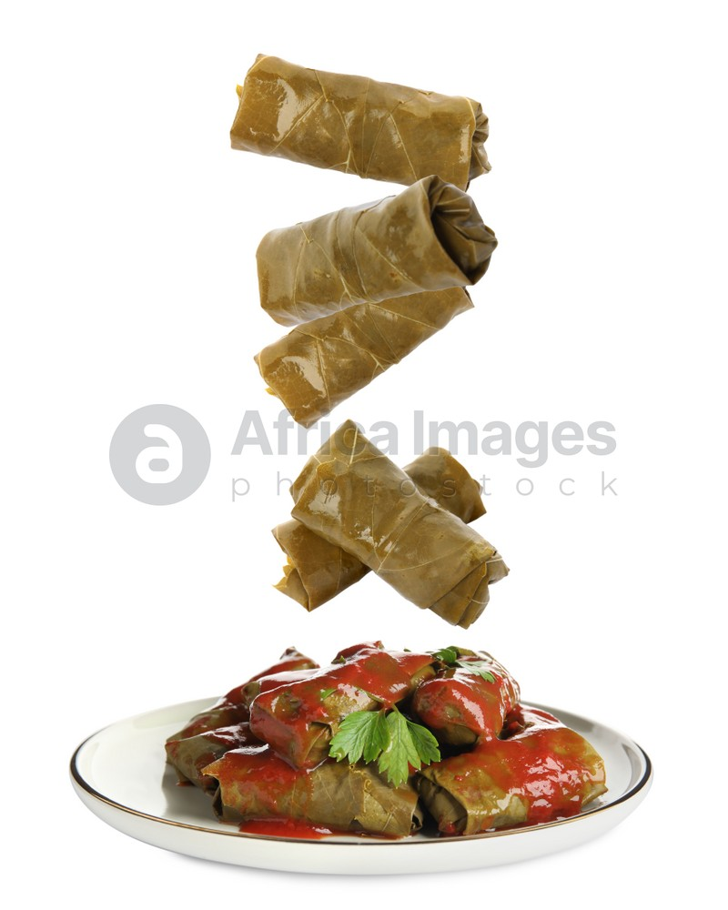 Delicious stuffed grape leaves falling into plate on white background