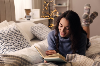 Young woman reading book at home. Winter atmosphere