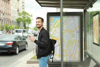 Young man with smartphone and backpack waiting for public transport at bus stop