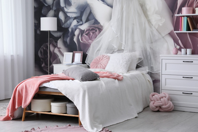 Teenage girl's room interior with comfortable bed and floral wallpaper. Idea for stylish design