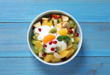 Delicious fruit salad on light blue wooden table, top view