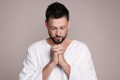 Religious man with clasped hands praying against grey background