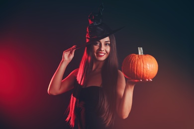 Young woman wearing witch costume with pumpkin on dark  background. Halloween party